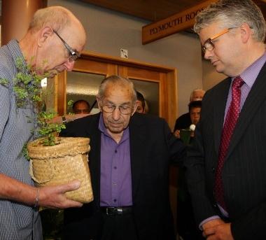 Hugh Johnstone (L) receives a kowhai from Mayor Judd (R) while Kaumata Rangikotuku Rukuwai says a karakia
